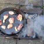 Fleisch auf offenen Feuer in er Pfanne anbraten.